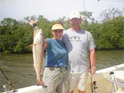 Red fish caught by adult couple on Marco Island Bay aboard Fins n Grins charter fishing boat